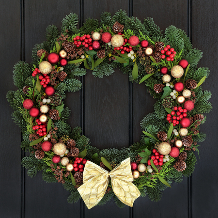 pine wreath: Christmas wreath with red and gold bauble decorations, bow, holly, mistletoe, pine cones and blue spruce fir over dark wood front door background.