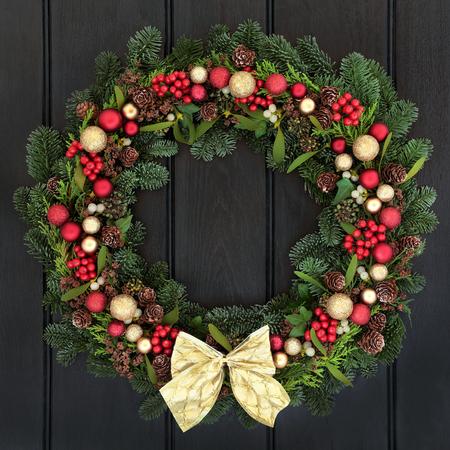 motivos navideños: Corona de Navidad con rojo y oro decoraciones de navidad, Lazo, acebo, muérdago, piñas de pino y abeto abeto azul sobre fondo de madera oscura puerta principal. Foto de archivo