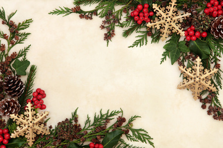 gold christmas decorations: Christmas background border with gold snowflake bauble decorations, holly, ivy and winter greenery over old parchment paper.