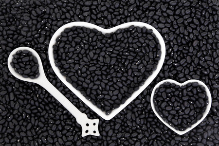 turtle bean: Black bean super health food in porcelain heart shaped dishes and spoon forming an abstract background. Stock Photo
