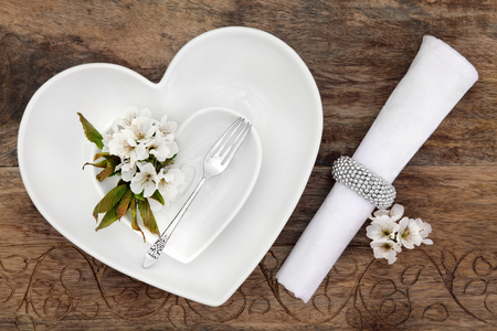 hearts and flowers: Romantic table place setting with white heart shaped porcelain bowls, antique silver fork with flower blossom and napkin with ring over old oak background.