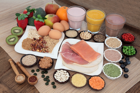 fish: Health and body building food with fish and meat, supplement powders, vitamin tablets, pulses, nuts, vegetables, fruit and high protein and juice smoothie shakes. Stock Photo