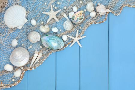 Zeeschelp abstracte collage met een visnet over houten blauwe achtergrond. Stockfoto