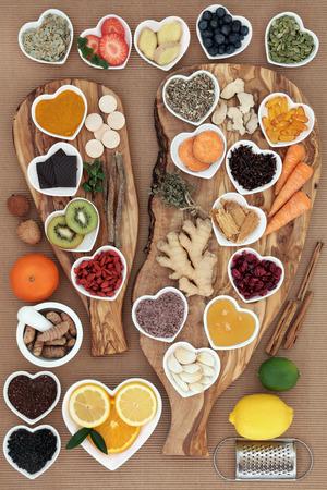 and medicine: Gran s�per alimento y selecci�n de hierbas medicinales para el remedio para el resfriado con alimentos ricos en antioxidantes en los tablones de madera de olivo sobre fondo blanco.