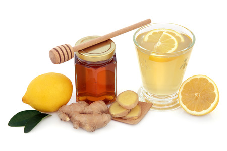 Cold and flu remedy cure with relief drink of ginger, lemon and honey over white background.