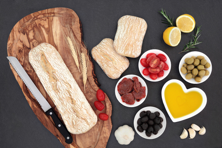 sundried: Mediterranean food with olives, fresh and sundried tomatoes, garlic, lemon, oil and ciabatta bread on olive wood board with wheat sheaths and rolls. Stock Photo
