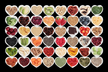 dried fish: Large superfood fruit and vegetable selection in heart shaped dishes over black background. High in antioxidants, vitamins, protein and dietary fibre. Stock Photo