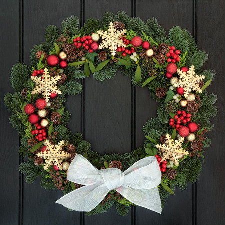 door: Christmas wreath with gold snowflake and red bauble decorations, holly, mistletoe and winter greenery over dark oak front door background.