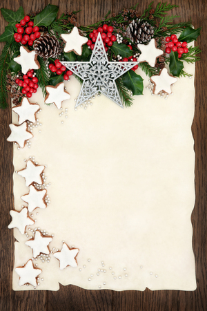 christmas cookies: Christmas background border with gingerbread cookies, silver star and ball decorations, holly, ivy, fir and pine cones on parchment paper over old oak wood.