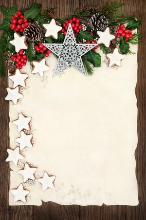 galletas de navidad: frontera del fondo de Navidad con galletas de jengibre, estrella de plata y adornos de bolas, acebo, hiedra, abeto y piñas en el papel de pergamino sobre la madera de roble viejo. Foto de archivo