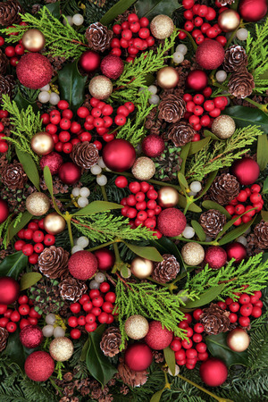 gold decorations: Christmas abstract background with red bauble decorations, holly, ivy, mistletoe, blue spruce fir and cedar cypress greenery.