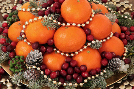 gold christmas decorations: Christmas satsuma orange and cranberry fruit, gold bead decorations, holly, mistletoe and winter greenery over oak background.
