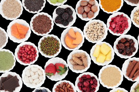 superfood: Health and superfood selection in porcelain crinkle bowls over black background. High in vitamins and antioxidants. Stock Photo