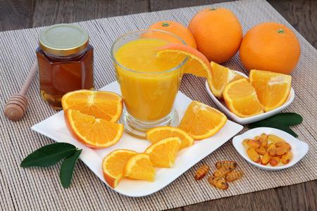 fruit orange: Con productos naturales para el alivio cura fría con zumo recién exprimido de fruta de naranja, tabletas de vitamina C y la miel en bambú sobre el fondo de roble. Foto de archivo