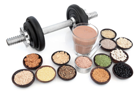 Body building dumbbells with health and super food of chocolate whey, red maca and wheat grass supplement powders, pulses, seeds, nuts, grains and protein shake over white background.