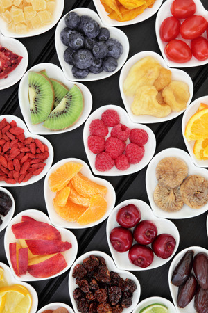 superfood: Fresh and dried mixed fruit superfood selection in heart shaped bowls over wooden black background.
