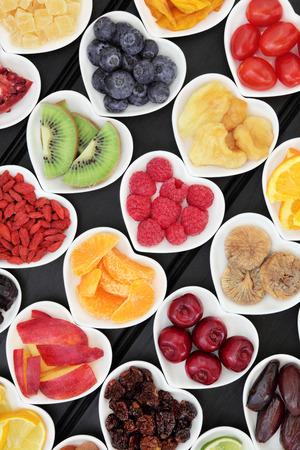 frutas tropicales: Selección súper fruta mezclada fresca y seca en forma de corazón sobre fondo negro cuencos de madera.
