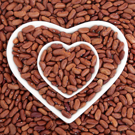 pinto bean: Pinto bean health food in heart shaped bowls forming an abstract background. Stock Photo