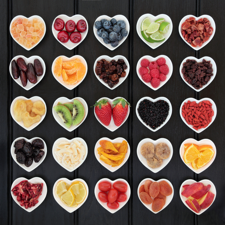 superfood: Superfood fruit selection in heart shaped bowls over wooden black background.