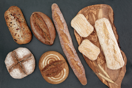 malted: Homemade bread selection on olive wood board on slate background.
