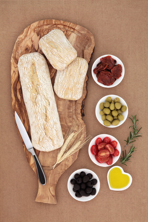 ridged: Picnic food and antipasti with olives, sundried and fresh tomatoes, olive oil, with ciabatta bread, wheat sheaths and knife on a wooden board with rolls on brown ridged paper background.