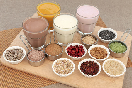 body building: Body building health food with protein and fruit juice shakes, chocolate whey, wheatgrass, pomegranate and maca powder, seeds and oatmeal on a beech wood board. Stock Photo