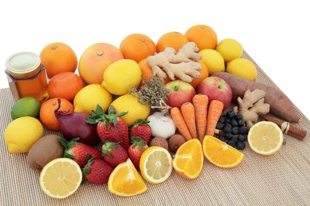 gripa: Amplia selección de alimentos saludables para el remedio para el resfriado y la gripe con alimentos ricos en antioxidantes y vitamina c en bambú sobre fondo blanco.
