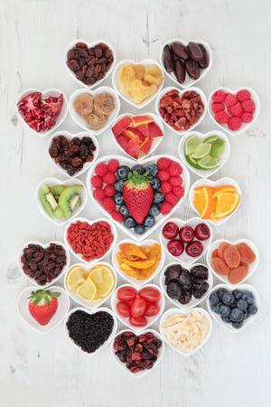 vitamin c: Fruit superfood background selection with fruits high in antioxidants, vitamin c and dietary fibre in heart shaped bowls over distressed white wood.