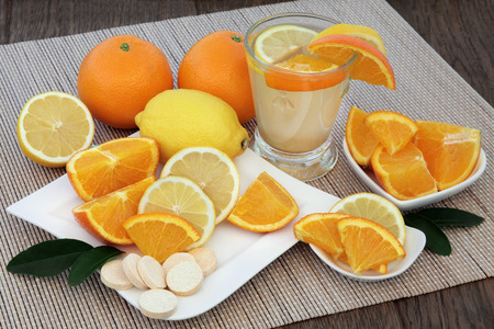 vitamin c: Cold and flu health remedy drink with orange and lemon fruit and vitamin c tablets on bamboo over oak background.