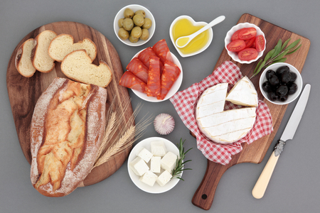 rustic food: Fresh food selection with chorizio, camembert and feta cheese, olives, tomatoes, oil, herbs and rustic bread on maple boards.
