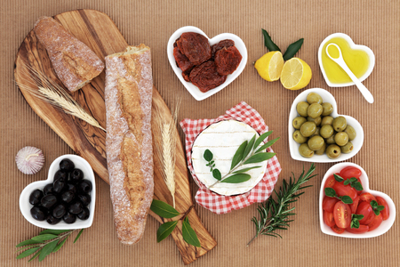 Picnic food with french baguette loaf on an olive wood board, camembert cheese, olives, sundried and fresh tomatoes, oil, lemon, garlic and herb leaf sprigs.