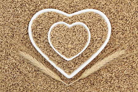 oats: Oat groat health food cereal grain in heart shaped bowls with wheat sheaths forming an abstract background.