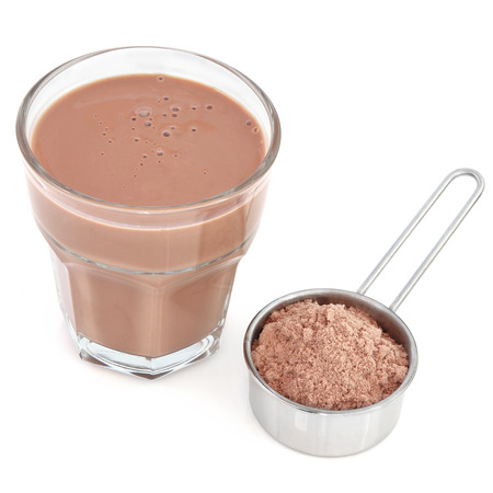 Chocolate whey protein drink with powder in a metal measuring scoop over white background.
