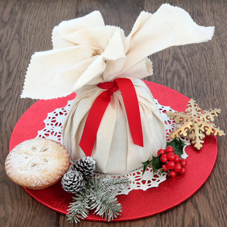 doiley: Christmas mince pies with pudding in a muslin bag, holly, winter greenery and snowflake bauble over oak background.