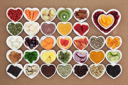 Gezondheid voedsel voor griep en verkoudheid te verhelpen kuren hoog in antioxidanten en vitamine c met tabletten, geneeskrachtige kruiden en specerijen in hart gevormde gerechten.