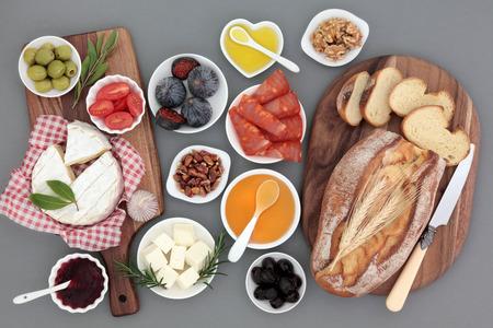 pan frances: Comida de picnic naturaleza muerta con carne, queso, frutas, verduras, mermelada, miel y hierbas con r�stico del pan franc�s en los tablones de arce. Foto de archivo
