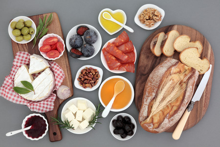 food still: Picnic food still life with meat, cheese, fruit, vegetables, jam, honey and herbs with rustic french bread loaf on maple boards. Stock Photo