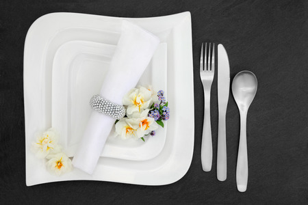 porcelain flower: Elegant table place setting with white porcelain dishes, stainless steel cutlery, spring flower selection and  napkin with silver ring over slate background.