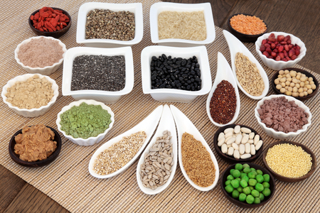 Health and body building super food with whey protein, wheat grass, acai berry and maca powder, nuts, seeds, pulses, grains, cereals, fruit, vegetables and peanut butter. Stock Photo