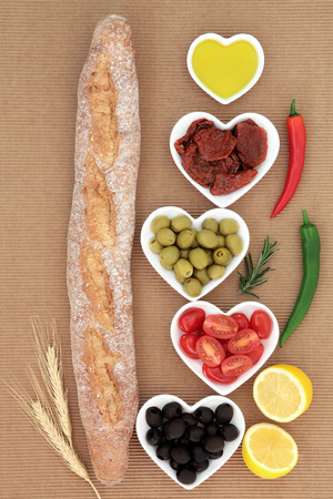 antipasti: French baguette bread loaf with antipasti selection of fresh and sundried tomatoes, green and black olives, chilli peppers, olive oil and lemon halves. Stock Photo