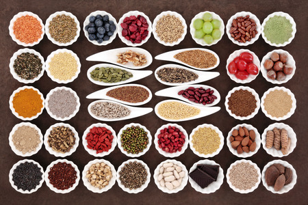 selection: Health and diet superfood food selection in porcelain bowls over lokta paper background. High in vitamins and antioxidants.