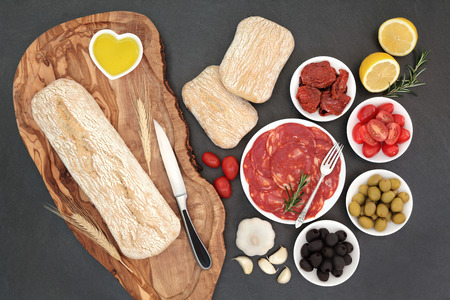 antipasti: Antipasti with olives, salami, sundried and fresh tomatoes, garlic, lemon, oil, with ciabatta bread on an olive wood board with rolls on slate background.