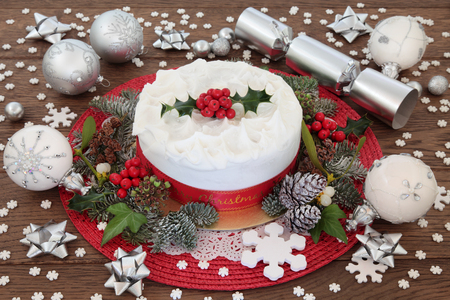 dundee: Christmas cake with holly, bauble decorations and winter greenery over oak background.