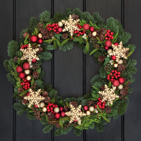 gold christmas decorations: Christmas wreath with gold snowflake bauble decorations, holly, mistletoe and winter greenery over dark oak front door background. Stock Photo