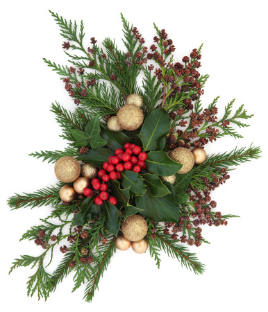 gold christmas decorations: Christmas flora with gold bauble decorations, holly, ivy and winter greenery over white background.