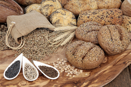 wholemeal: Seeded bread roll selection with wheat sheaths, rye grain in a hessian sack with chia, sunflower and caraway seed on an olive wood board.