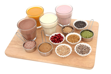 body milk: Body building health food with protein and fruit juice shakes, chocolate whey, wheatgrass, pomegranate and maca powder, seeds and oatmeal on a beech wood board over white background.