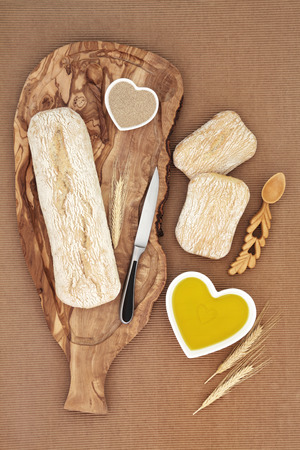 sheath: Italian ciabatta bread loaf on an olive wood board with yeas. knife and wheat sheath, with rolls and oil in a heart shaped bowl.