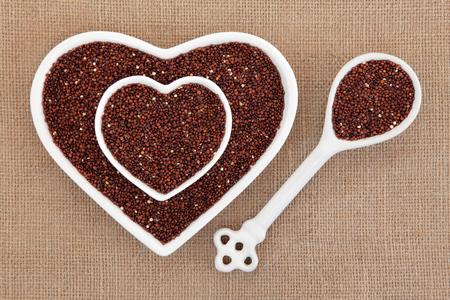 super food: Quinoa grain super food in heart shaped bowls and porcelain spoon over hessian background. Salvia hispanica. Stock Photo