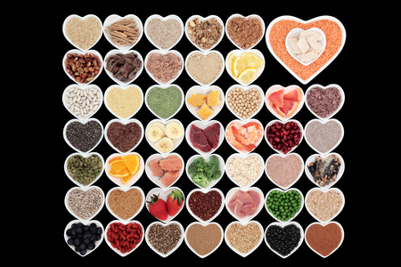 super fruit: Large health and body building high protein super food in heart shaped bowls with meat, fish, supplement powders, seeds, cereals, grains, fruit and vegetables.